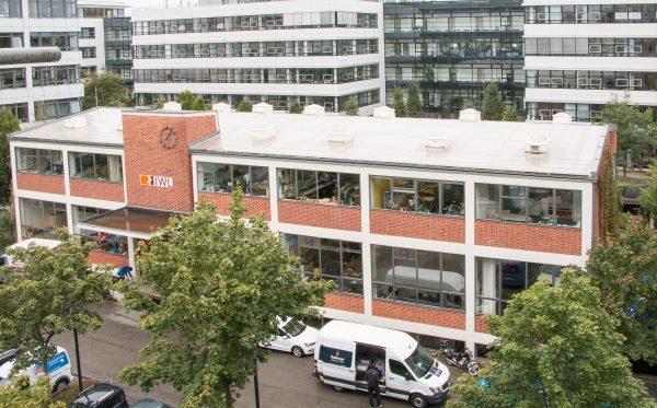 Gebäude der IWL München, ein Gebäude aus weißen und roten Ziegeln und einem großen IWL-Logo