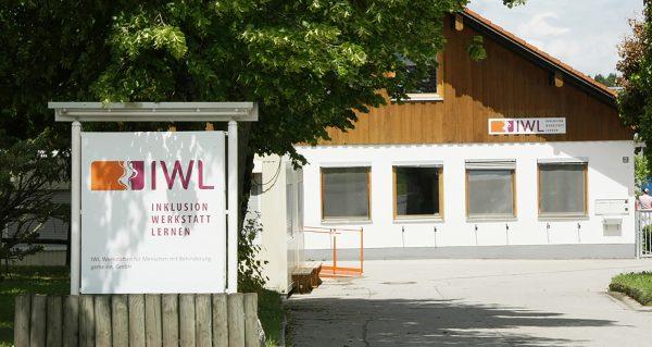 Das Gebäude der IWL Machtlfing mit einem großen Schild mit dem IWL Logo
